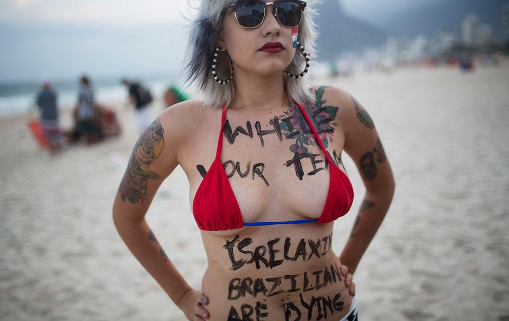ब्राजील के रियो डी जेनेरियो में इपानेमा बीच पर एंटी वर्ल्ड कप विरोध के दौरान पोज देते हुए कार्यकर्ता सारा विंटर।