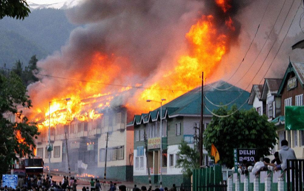 श्रीनगर से करीब 90 किमी. दूर पहलगाम में होटलों और शॉपिंग मॉल में लगी आग को बुझाने का प्रयास करते हुए अग्निशमन दल के कर्मी।