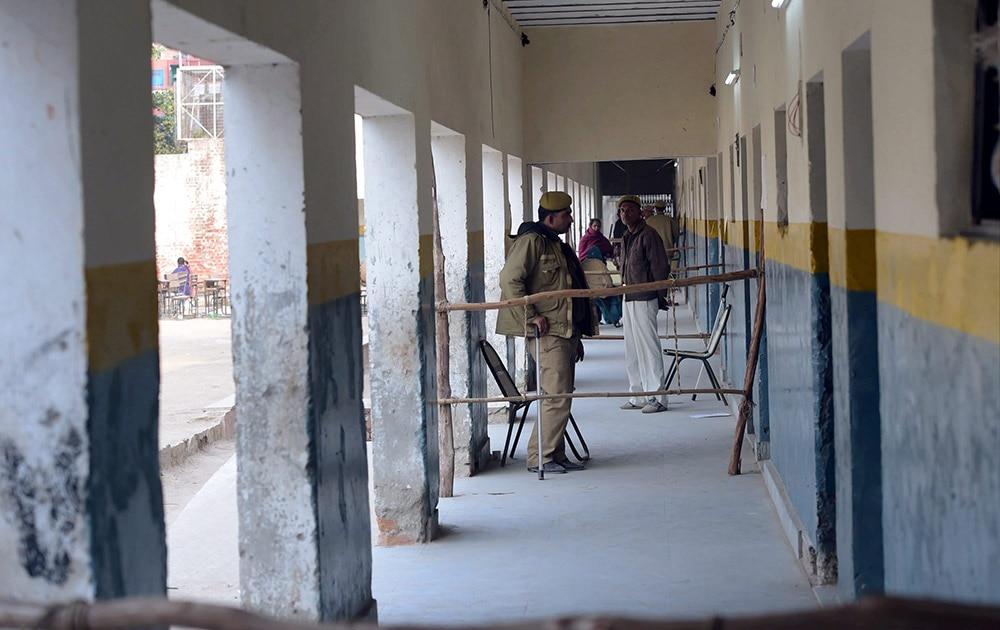 दिल्ली विधानसभा चुनाव के दौरान त्रिलोकपुरी में मतदान केंद्र के बाहर सुरक्षा कर्मी तैनात।