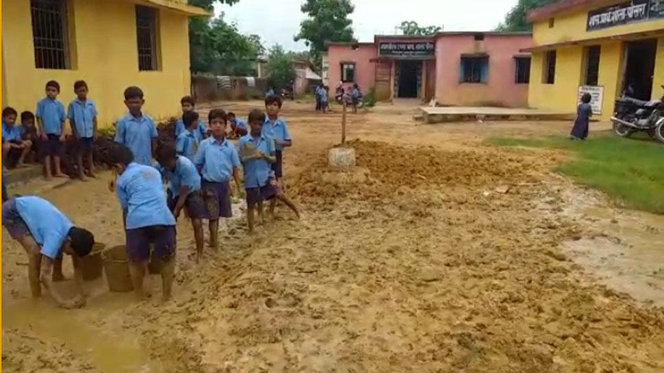 कीचड़ साफ करने के लिए शिक्षकों ने मासूम बच्चों के हाथ पकड़ा दिया फावड़ा