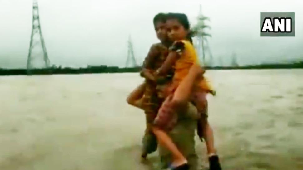उफनती लहरों के बीच बच्चों को कंधे पर बैठाकर 1.5 किमी पैदल चला पुलिस का जवान, VIDEO VIRAL