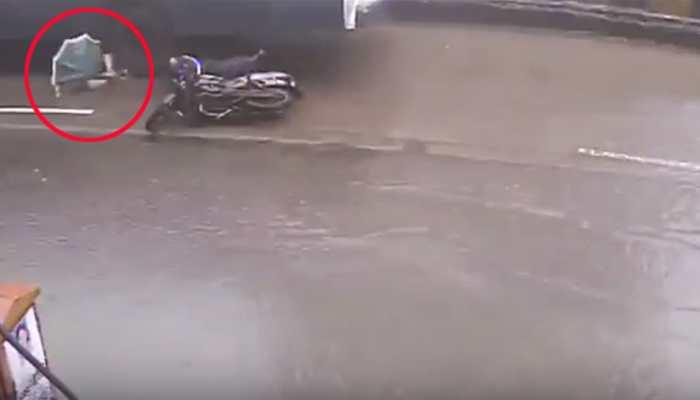 VIDEO: सड़क के गड्ढे ने ली महिला की जान, बाइक से गिरी तो बस ने कुचला