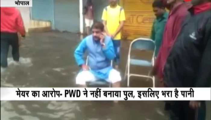 Bhopal Mayor Alok Sharma sits in the middle of a water logged street in protest