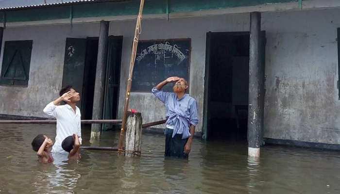 असम: कंधे तक बाढ़ के पानी में तिरंगे को सलामी देने वाले लड़के का नाम NRC ड्राफ्ट में नहीं