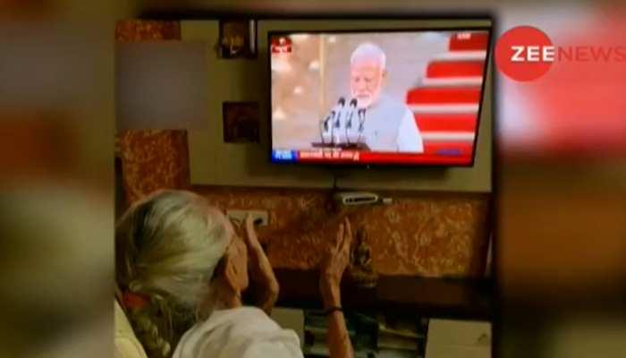 VIDEO: बेटे नरेंद्र मोदी को शपथ लेते देख कर खुश हुईं मां हीराबेन, टीवी देख बजाने लगीं ताली