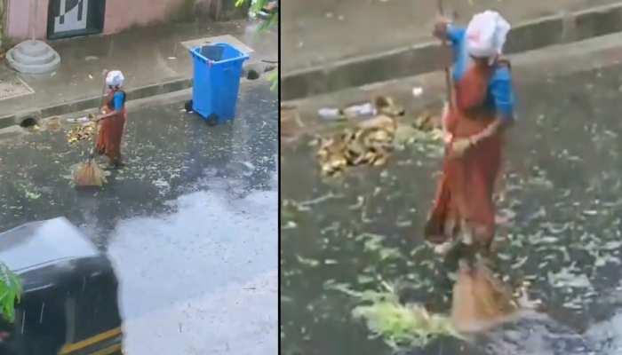 तूफान और बारिश में भीगते हुए महिला ने लगाई सड़क पर झाड़ू