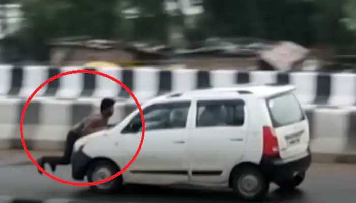 Video: बोनट पर लटका रहा शख्स, फिर भी ड्राइवर ने तेज रफ्तार में दौड़ा दी कार